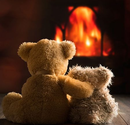Teddy bears in front of warm fire.